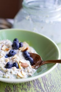 image of simple-overnight-oats by intentionally eat in a green bowl topped with blueberries and almonds