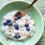 image of simple overnight oats by Intentionally Eat with Cindy Newland in a green bowl with a gold spoon and blueberries