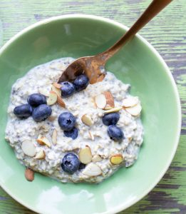 image of simple-overnight-oats by intentionally eat in a green bowl with a copper spoon and topped with blueberries and slivered almonds