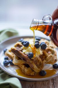 image of perfect protein waffles by intentionally eat with maple syrup being poured over waffles covered in blueberries