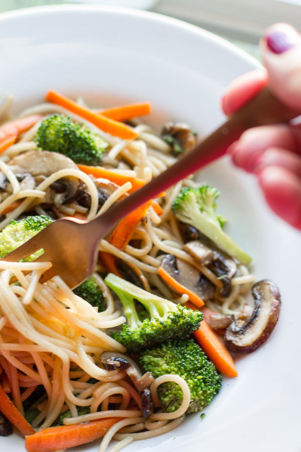 image of Easy Vegetable Lo Mein by Intentionally Eat with Cindy Newland in a white bowl with a hand holding a fork twirling noodles