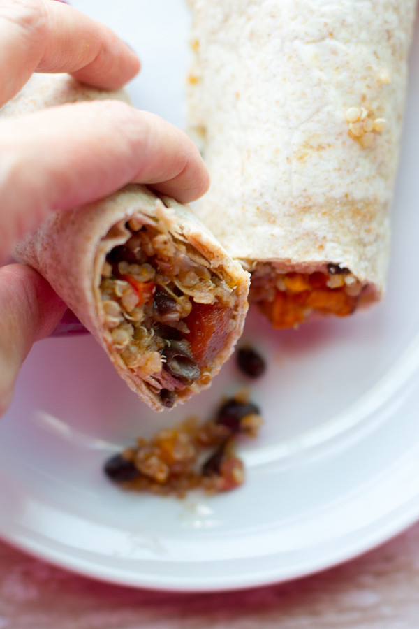 image of Quinoa Sweet Potato and Black Bean Burritos by Intentionally Eat with Cindy Newland with a hand holding half a burrito