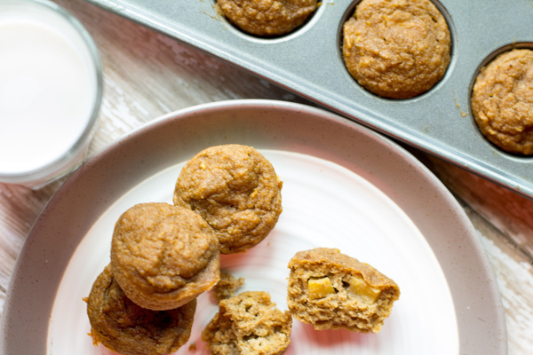 image of healthy cinnamon apple muffins by intentionally eat with cindy newland on a plate with a glass of almond milk and muffin tin next to it