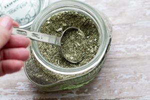 Homemade Dry Ranch Seasoning Mix by Intentionally Eat with Cindy Newland in a glass jar with a silver tablespoon