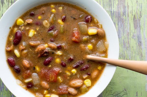 Skinny Taco Soup by intentionally Eat with Cindy Newland in a white bowl with a gold spoon