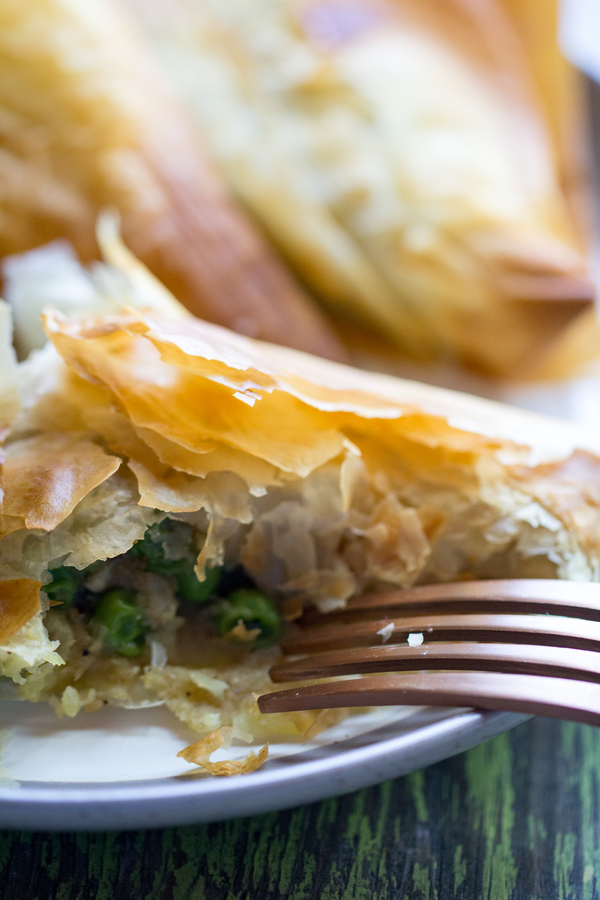 image of Easy Air Fried Vegetable Samosas by Cindy Newland with Intentionally Eat in a phyllo dough on a plate with a gold fork