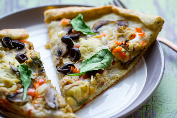 image of Homemade Greek Pizza by Intentionally Eat with Cindy Newland on a plate with a gold fork