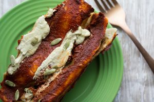image of Black Bean and Pumpkin Enchiladas by Intentionally Eat with Cindy Newland on a green plate with a gold fork