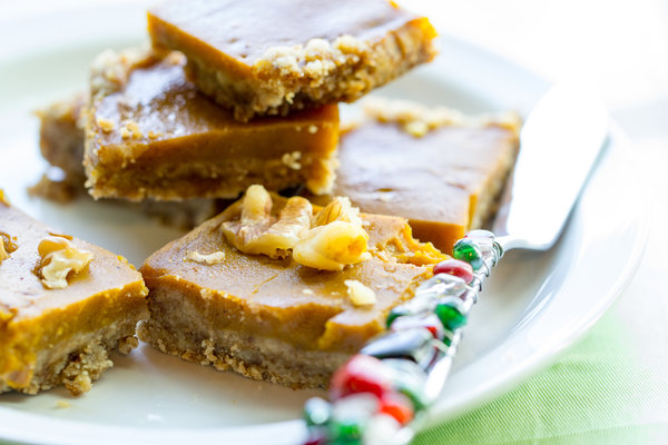 image of pumpkin pie bars with a gluten free crust by intentionally eat with cindy newland on a white plate