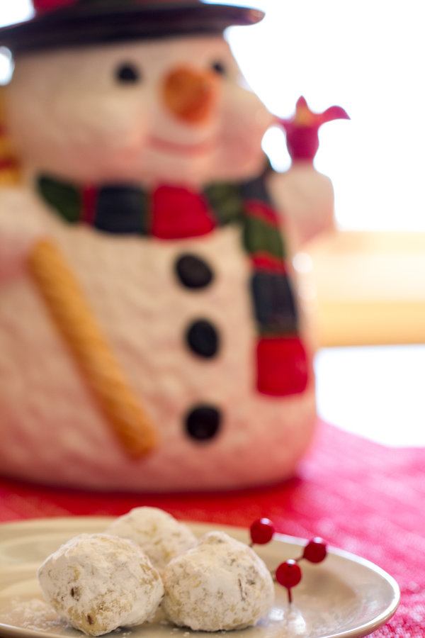 image of Healthy Snowball Cookies by Intentionally Eat with Cindy Newland on a plate snowman cookie jar in background