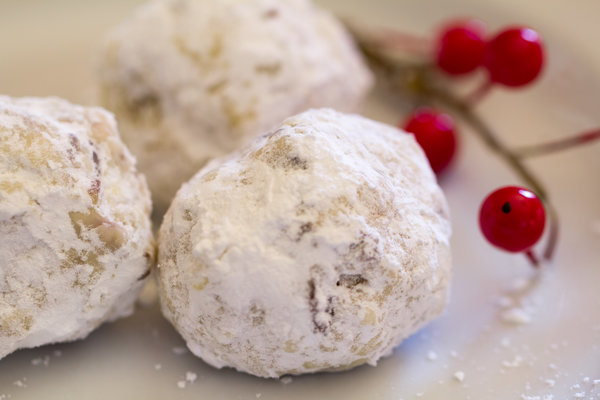 image of Healthy Snowball Cookies by Intentionally Eat with Cindy Newland on a plate with red berries