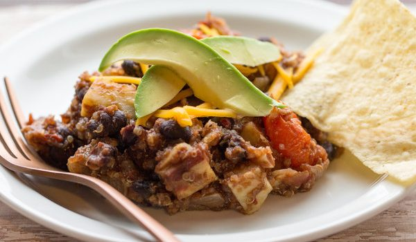 image of mexican quinoa skillet by intentionally eat with cindy newland on a white plate with tortilla chips, avocado and a fork