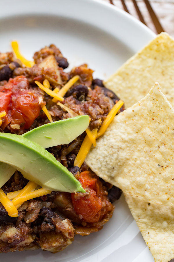 image of mexican quinoa skillet by intentionally eat with cindy newland on a white plate with tortilla chips, avocados and a fork