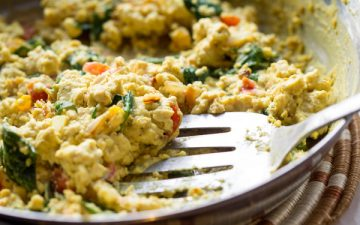 image of tasty tofu scramble by intentionally eat with cindy newland in a skillet with a spatula