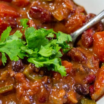 image of black bean pumpkin chili by Intentionally Eat with Cindy Newland in a white bowl with a spoon