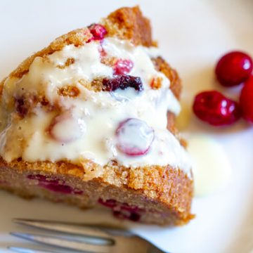 image of vegan cranberry bliss cake by intentionally eat with cindy newland on a white plate with a fork and cranberries