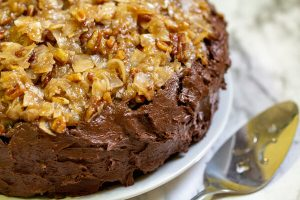 image of vegan german chocolate cake rich and easy by intentionally eat with cindy newland on a white plate with a cake server
