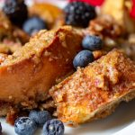 image of the ultimate healthy overnight french toast recipe by intentionally eat with cindy newland on a white plate with berries