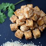image of fried tofu on a black plate sprinkled with sesame seeds
